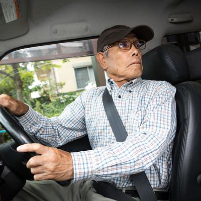 駐車中にアクセルとブレーキを間違えて慌てる高齢者の写真