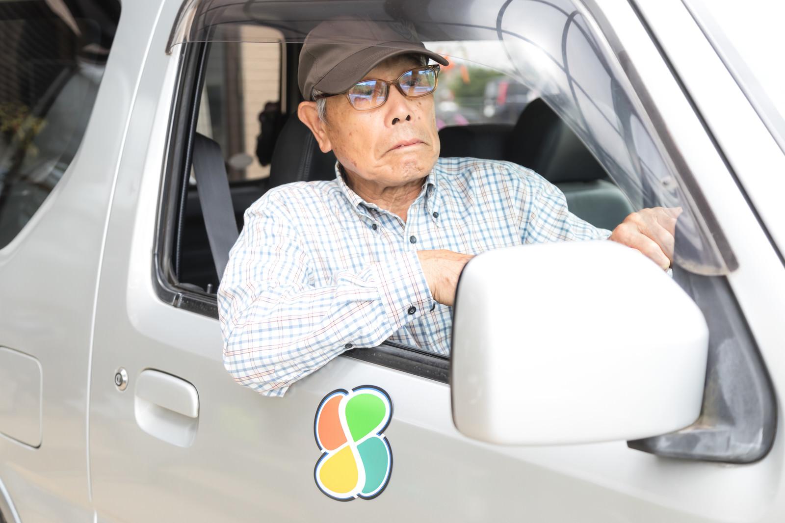 「なかなか前が進まなくてイライラする運転席のお爺さん」の写真[モデル:まーちゃん]