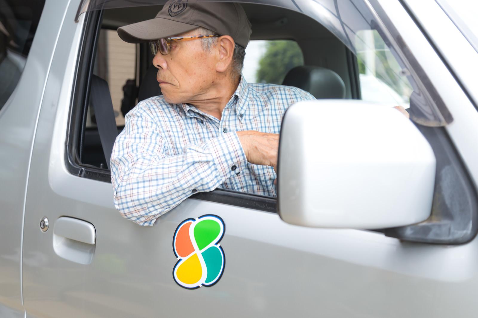「後方を目視で確認する高齢ドライバー」の写真[モデル:まーちゃん]