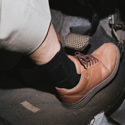 アクセルペダルを踏む高齢者の足元の写真