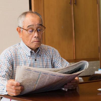 朝刊に目を通すお爺さんの写真