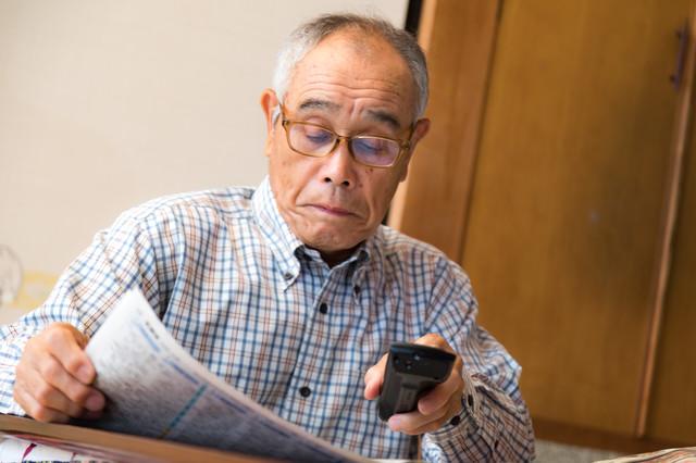テレビのリモコンを持ちながら新聞を読むシニアの写真