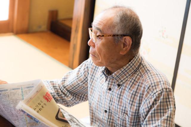 居間で新聞を読むお爺さんの写真