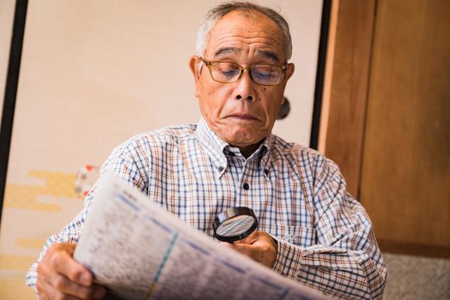 拡大鏡で新聞を読むおじいさんの写真