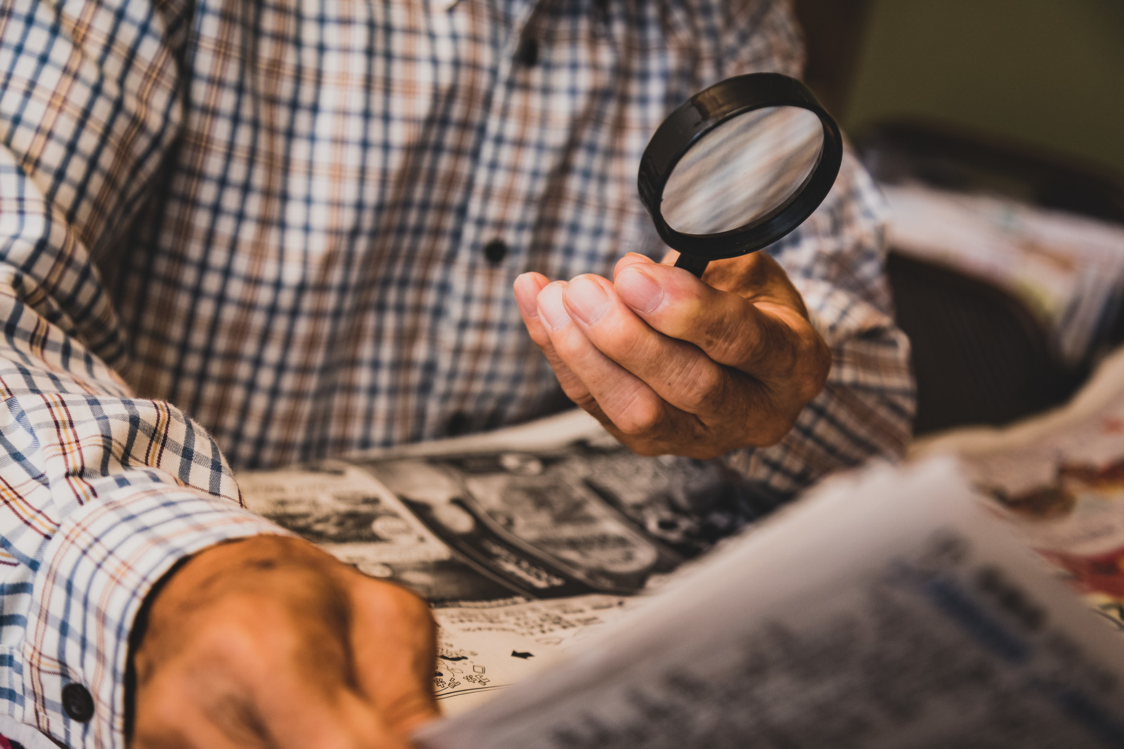 「新聞の文字が小さくて拡大鏡を使って読む(高齢者)」の写真[モデル:まーちゃん]