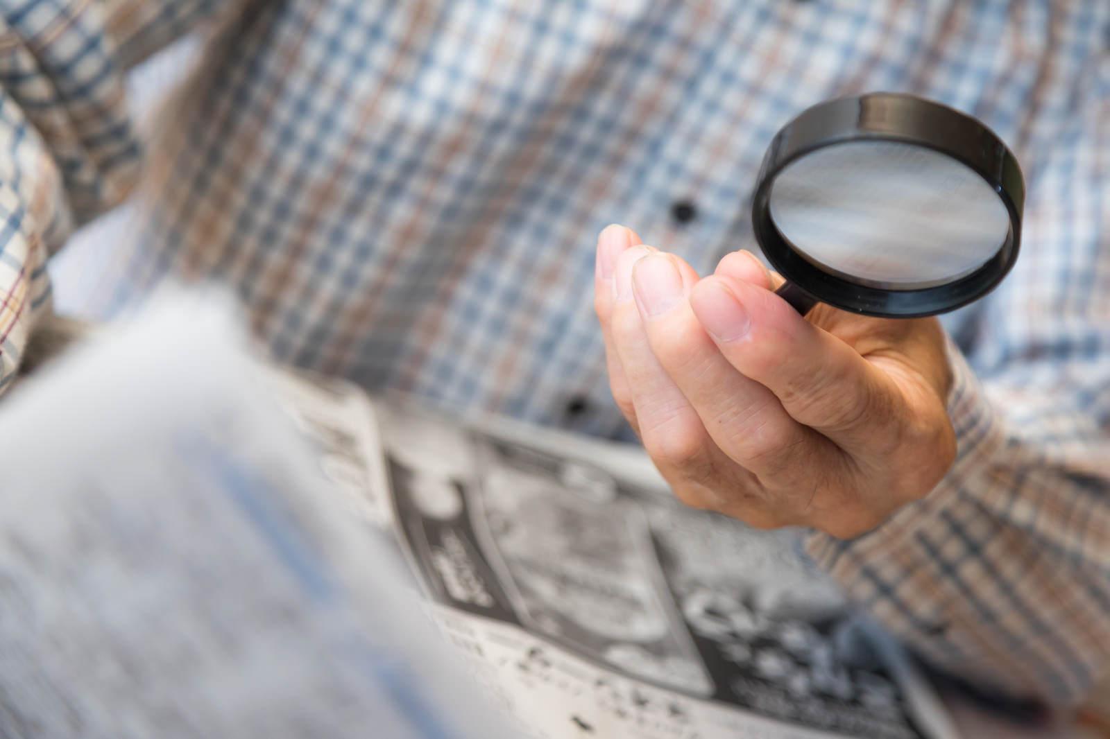 「手持ち拡大鏡で新聞を読む高齢者の手」の写真[モデル:まーちゃん]