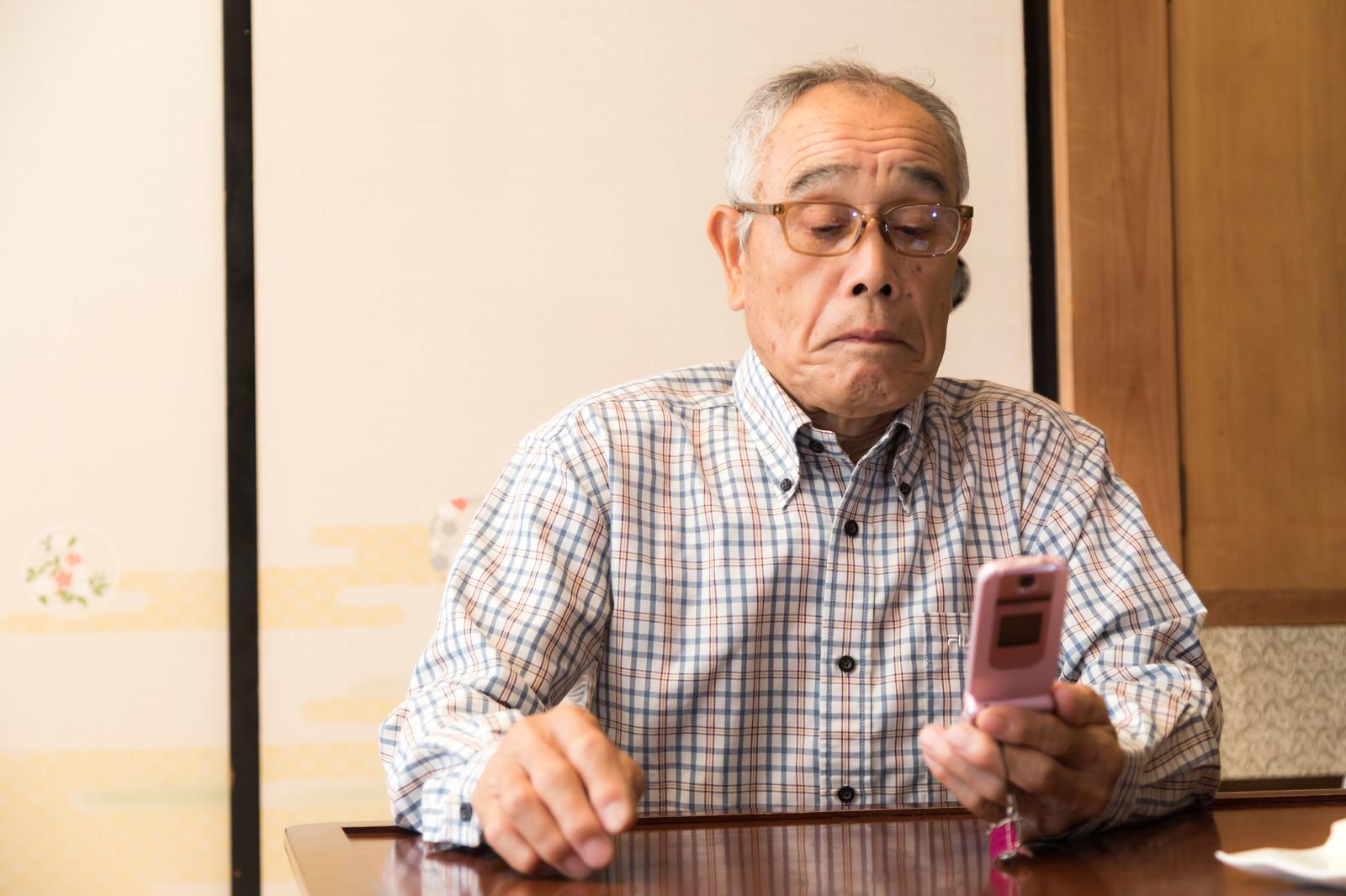 「ガラケーでメールを確認する田舎のじっちゃん」の写真[モデル:まーちゃん]