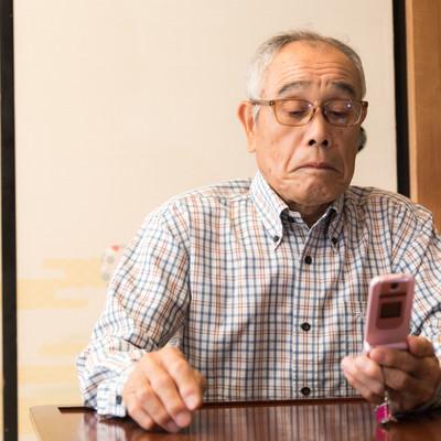 ガラケーでメールを確認する田舎のじっちゃんの写真