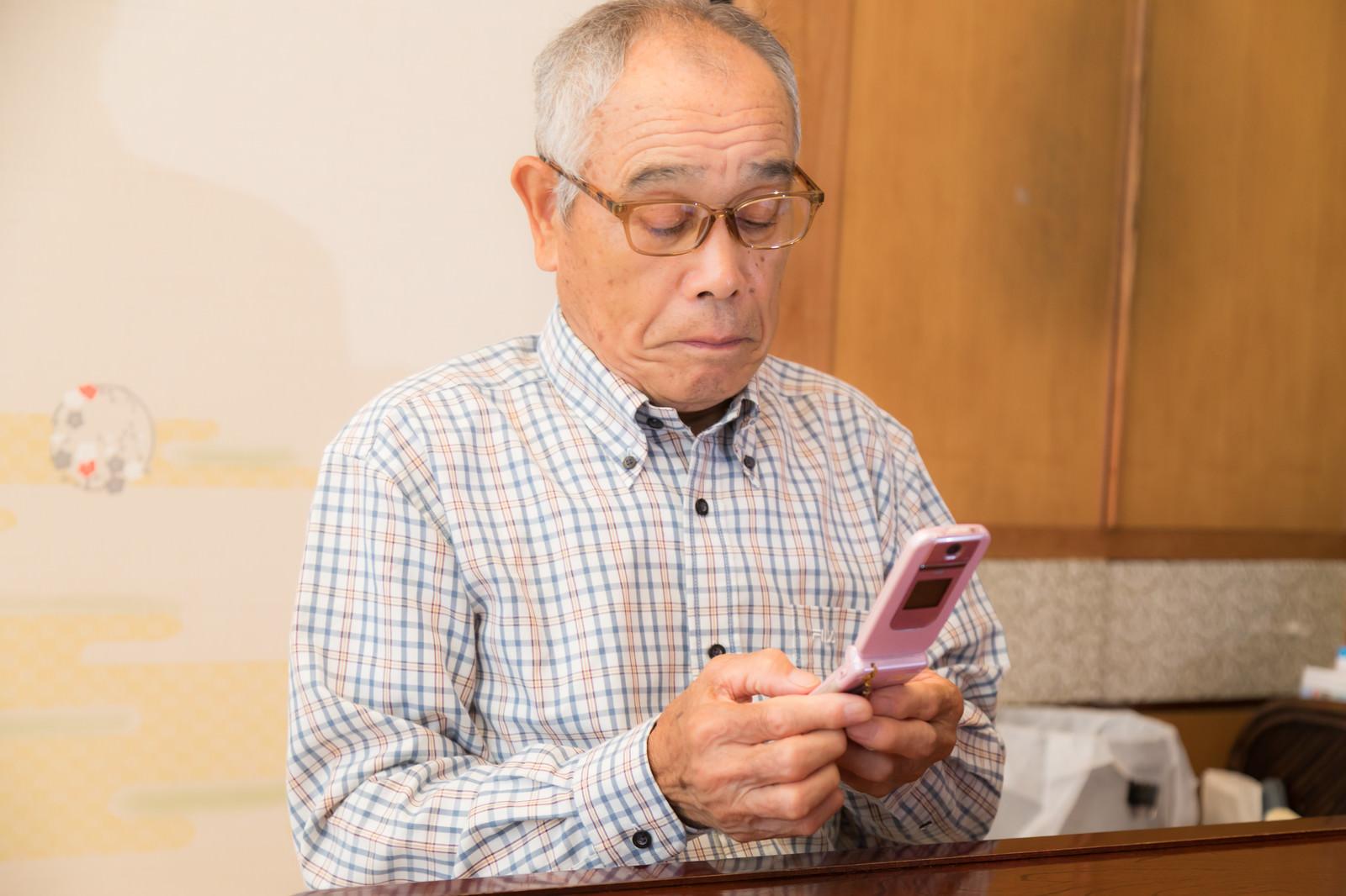 「必死にメールの返事をするお爺さん」の写真[モデル:まーちゃん]