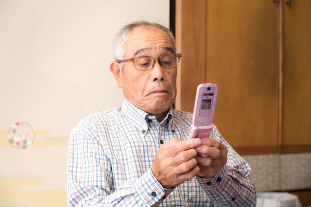 覚えたての携帯電話を使うお爺さんの写真