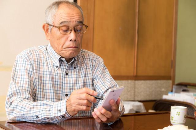 慣れない手つきでスマホを弄る高齢のお爺さんの写真