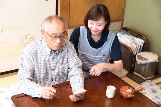 スマホの使い方を若い女性に習うお爺さんの写真
