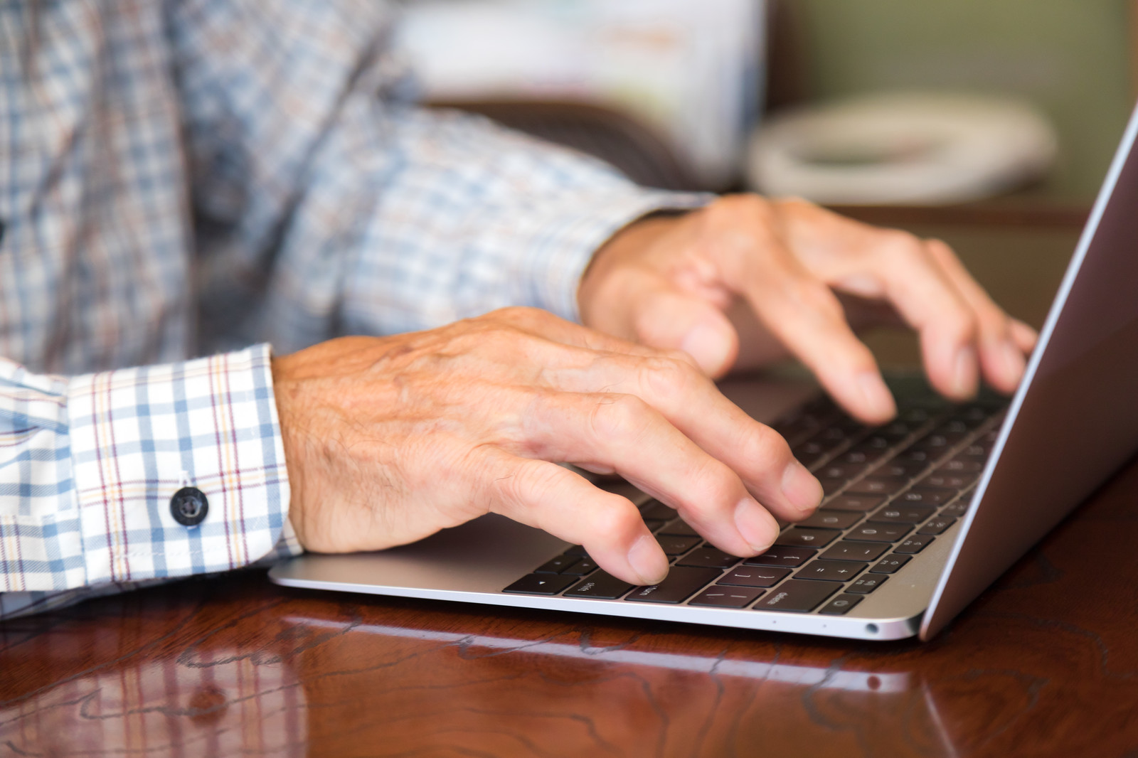 「慣れた手つきでタイピングする高齢者の手元」の写真[モデル:まーちゃん]