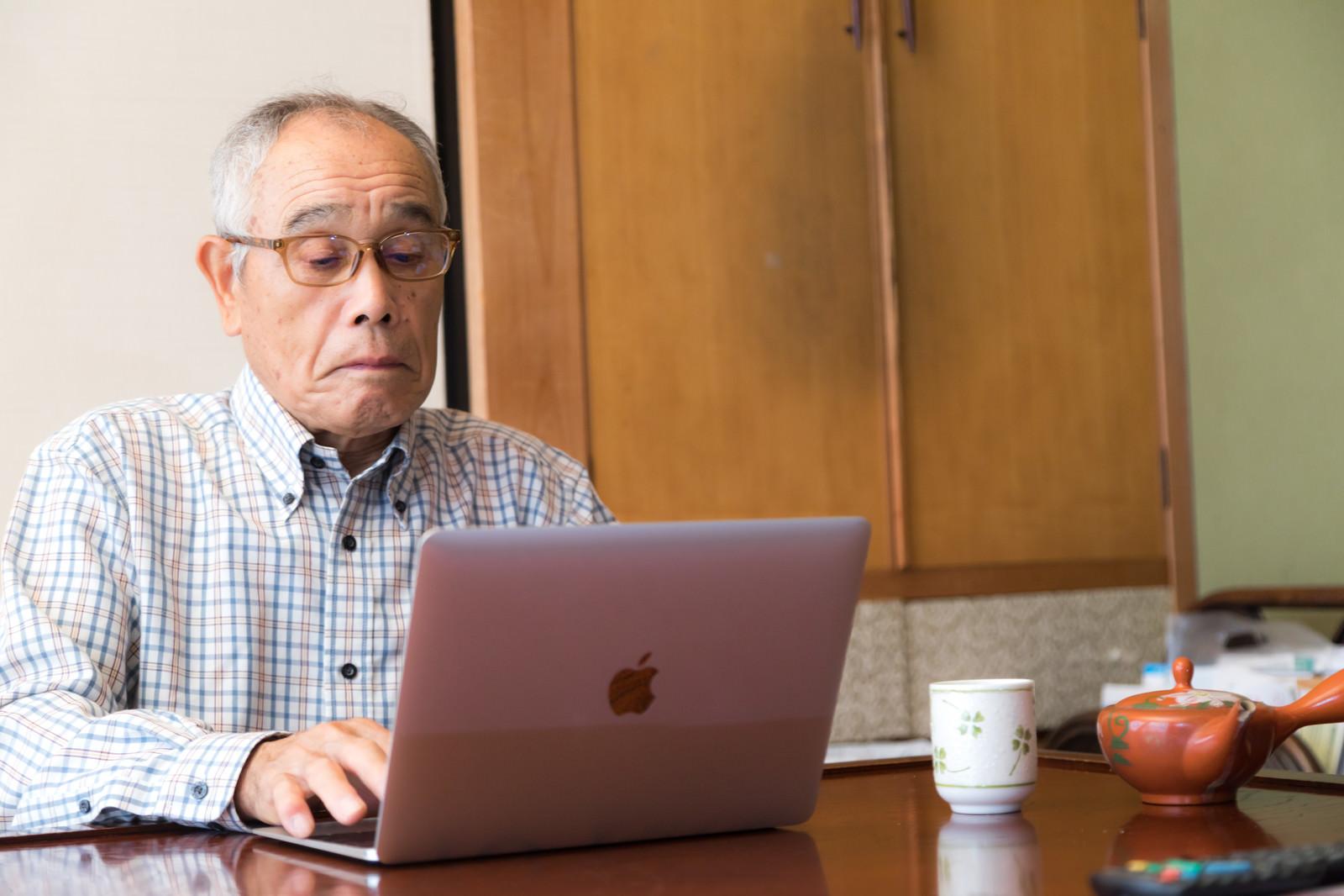 「株価のチェックに余念がない高齢者の男性 | 写真の無料素材・フリー素材 - ぱくたそ」の写真[モデル:まーちゃん]