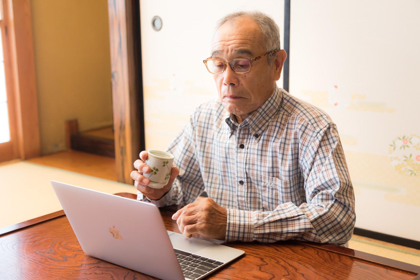 「ネットで動画を視聴する茶の間お爺さん」の写真[モデル:まーちゃん]