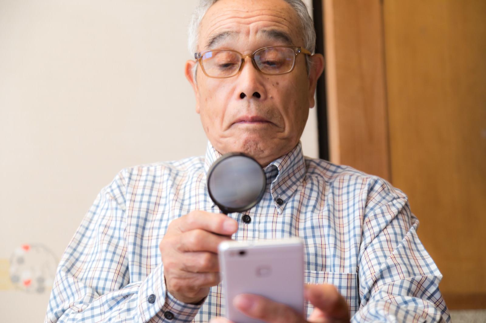 「携帯の画面が小さくて拡大鏡を使うおじいさん」の写真[モデル:まーちゃん]