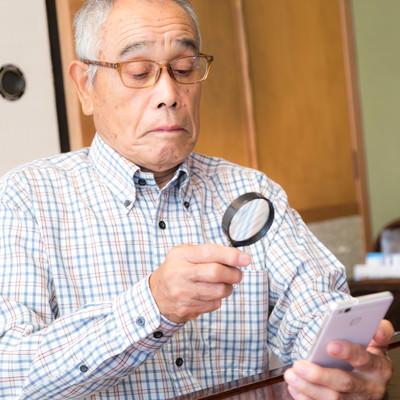 ガラケの文字サイズが小さいので拡大鏡を取り出す爺さんの写真