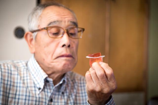 「祖父がこんにゃくゼリーを食べようとしています」のフリー写真素材