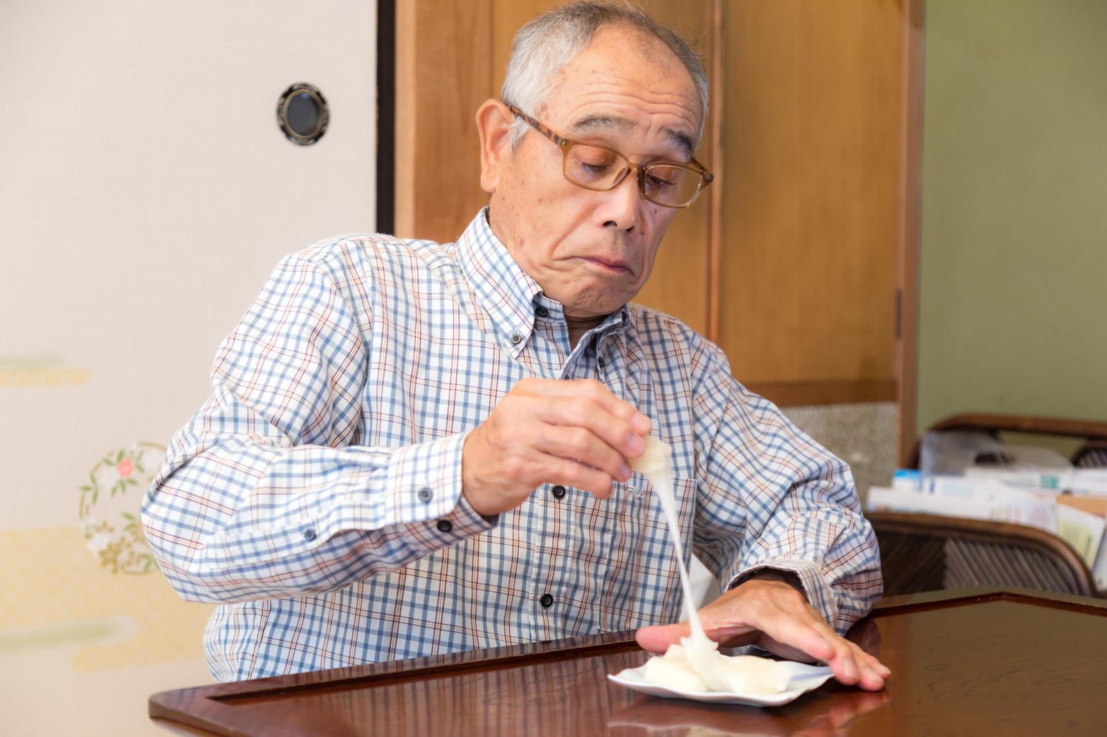 「手づかみで伸びるお餅を食べようとする爺さん」の写真[モデル:まーちゃん]