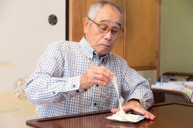 手づかみで伸びるお餅を食べようとする爺さんの写真