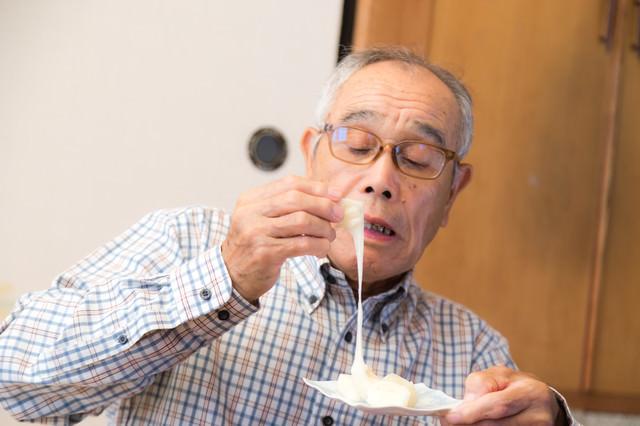 手づかみで伸びるお餅を食べる高齢者の写真