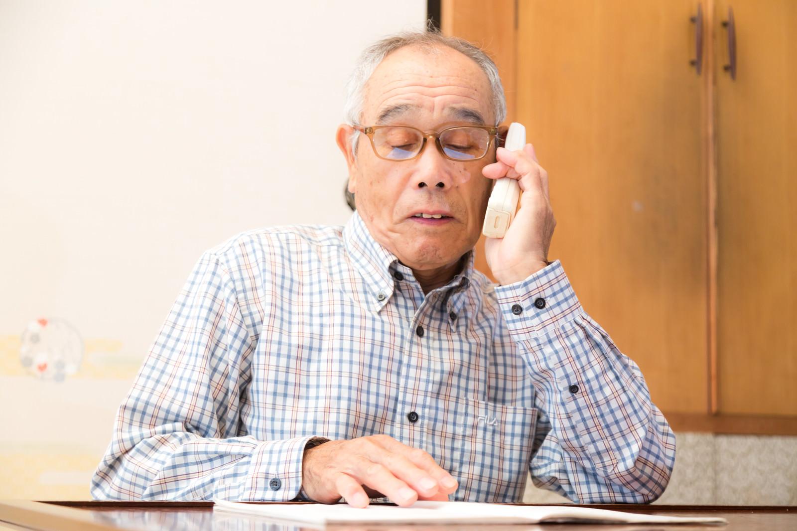「通販カタログを見ながら電話注文する高齢者」の写真[モデル:まーちゃん]
