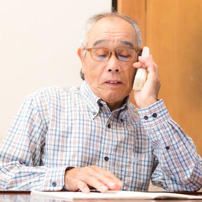 通販カタログを見ながら電話注文する高齢者の写真
