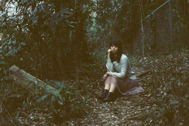 森のなかで座り込む女性の写真