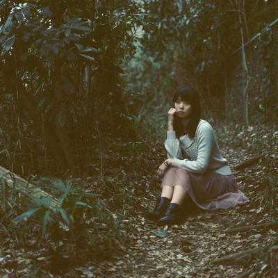 「森のなかで座り込む女性」の写真素材