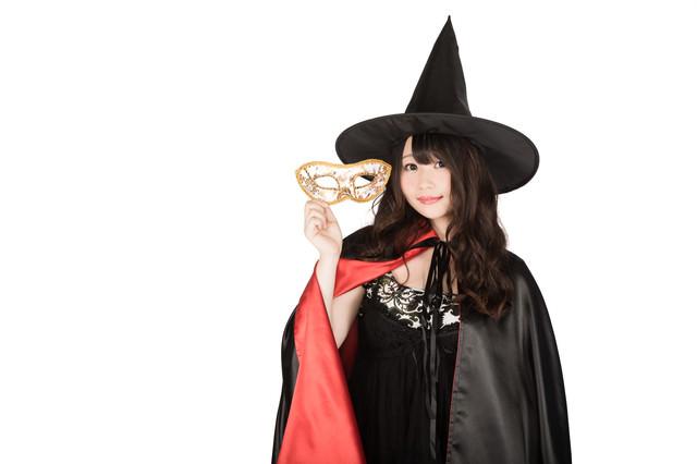 仮装用マスクを外した魔女(ハロウィン)の写真