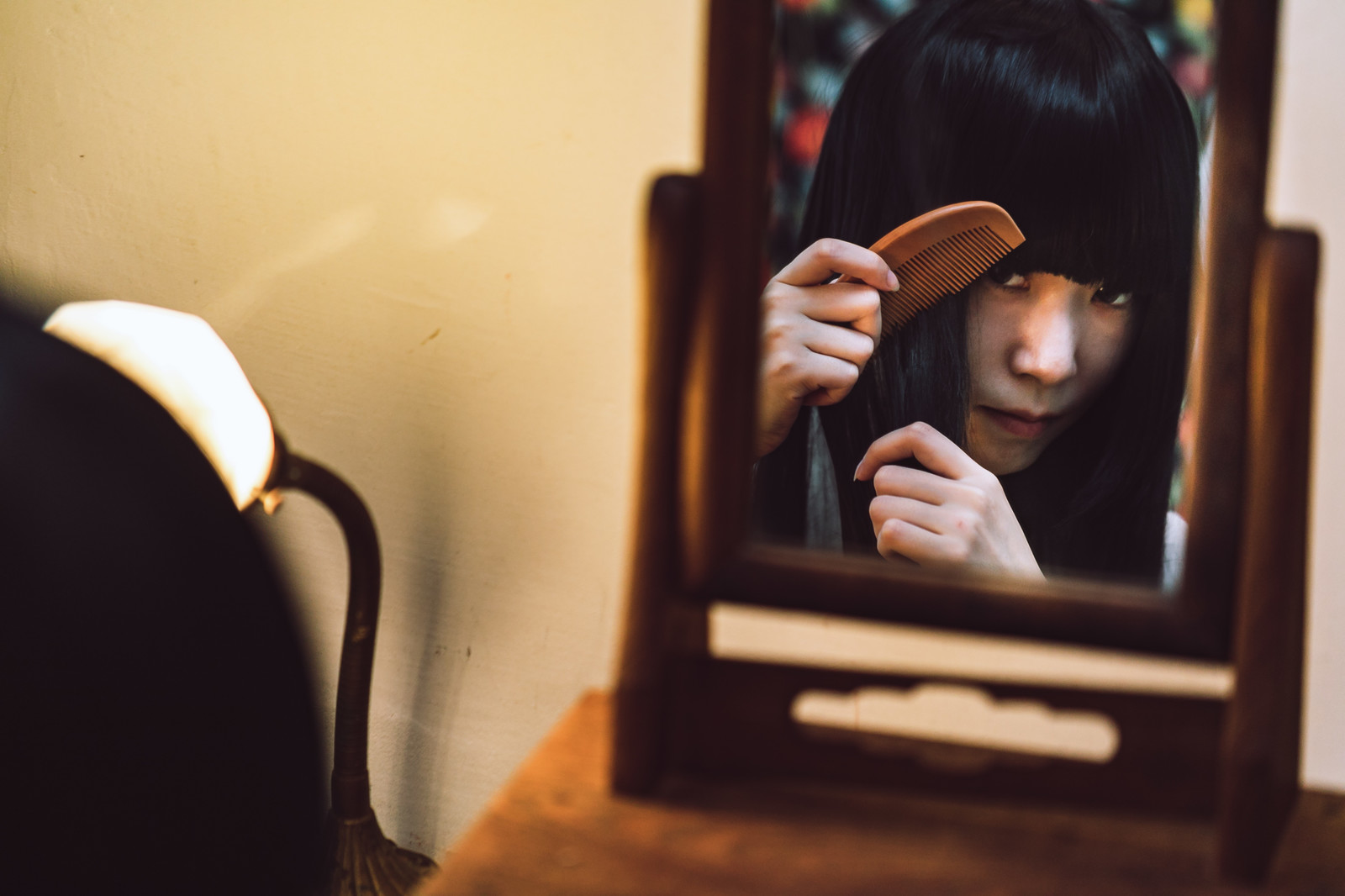 「化粧台の小さな鏡で櫛を通す女性」の写真[モデル:緋真煉]