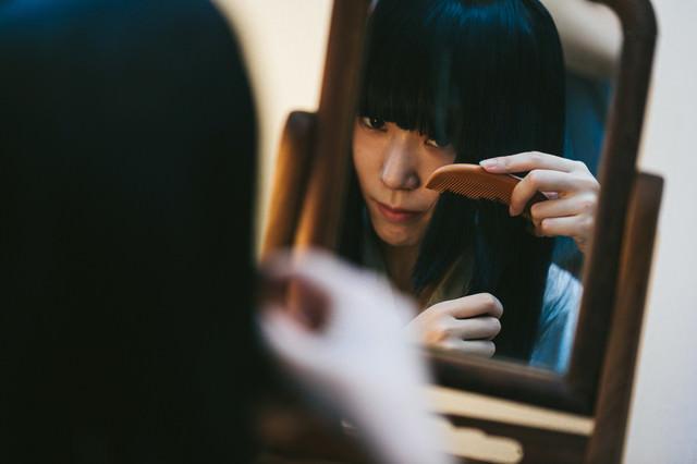 鏡を使って髪をとかす日本女性の写真