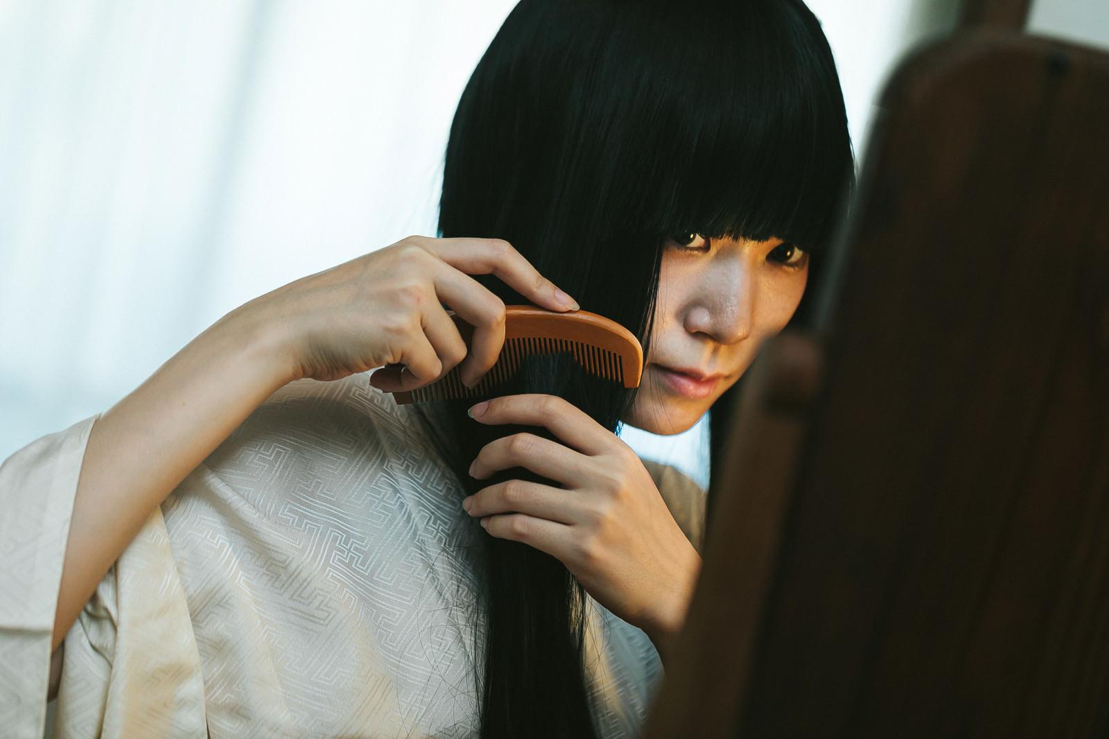 「長い黒髪をとかす女性」の写真[モデル:緋真煉]