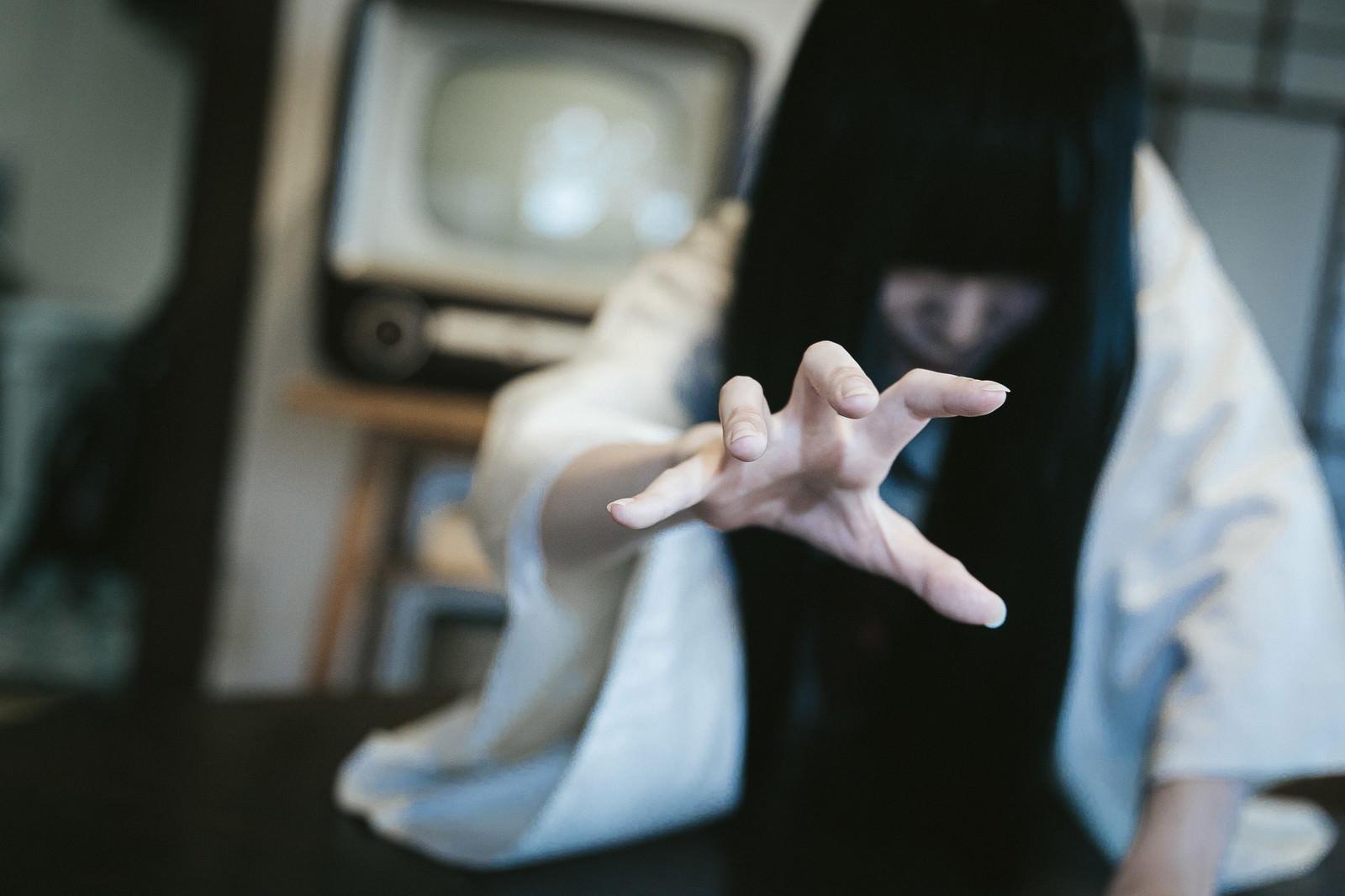 「視聴後にテレビから這い出てくる呪われた女性」の写真[モデル:緋真煉]