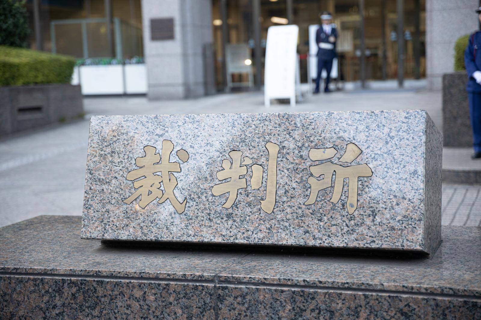 「裁判所を入り口を警備する警備員」の写真