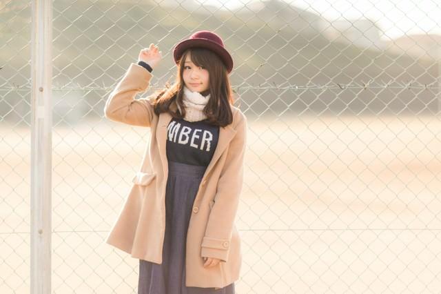 球場のフェンスとコートを着た美女の写真
