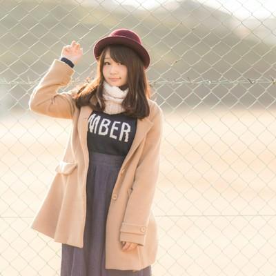 「球場のフェンスとコートを着た美女」の写真素材