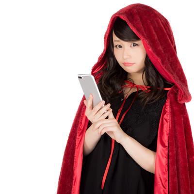 「赤いもこもこマントに仮装した美女」の写真素材