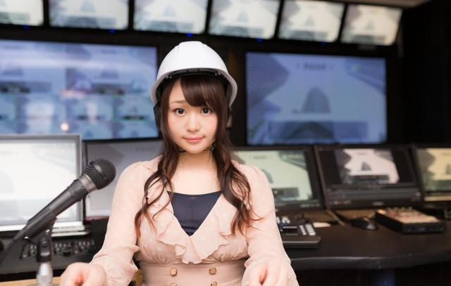ヘルメットを被りニュースを伝える女性アナウンサーの写真
