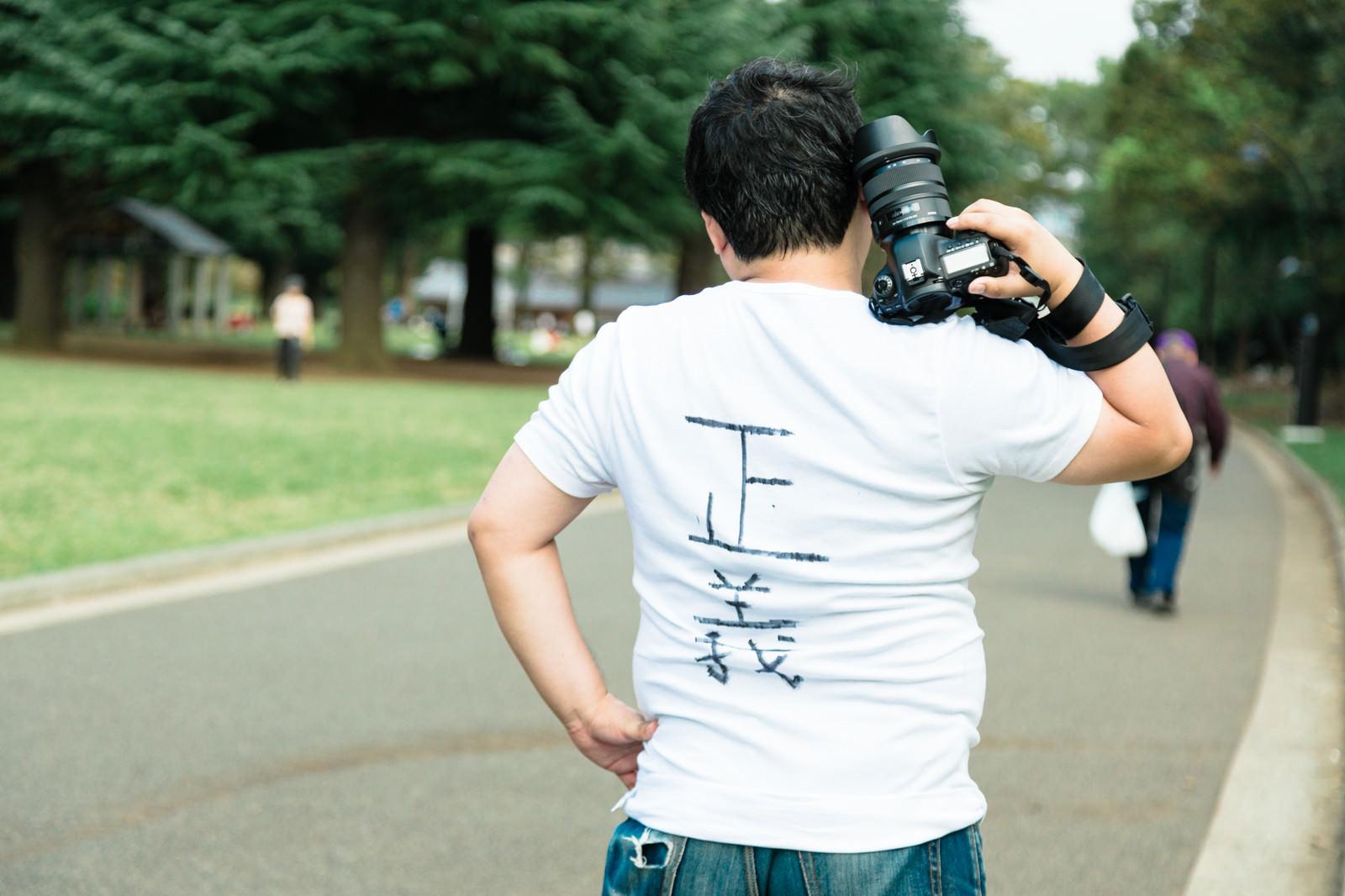 「ウンチクが多そうなカメラマンさんの後ろ姿」の写真[モデル:段田隼人]