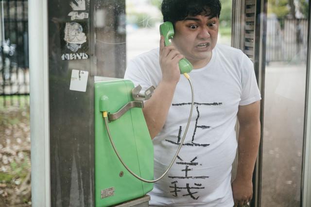 公衆電話から正義の通報をする男性の写真