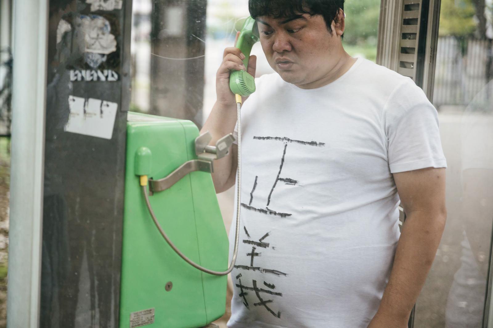 「公衆電話から匿名のタレコミをする男性」の写真[モデル:段田隼人]
