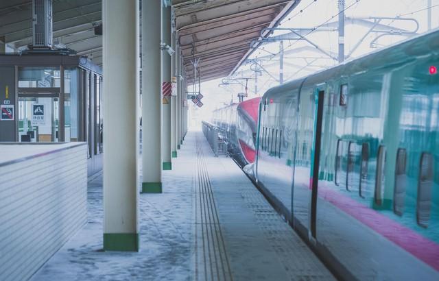 積雪とホームの電車の写真