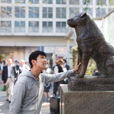 「女性を口説けず犬の銅像に慰めてもらうナンパ師」の写真素材