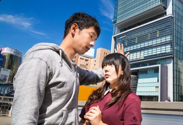 建物を壁に見立てた高度な壁ドンで女性を攻める男性の写真