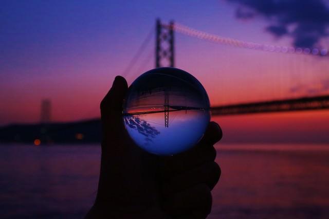 夕暮れ時のブリッジと反転して映る水晶球の写真