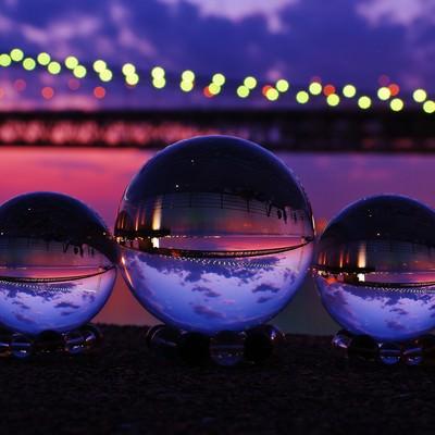 ライトアップした大橋と映り込む水晶球の写真