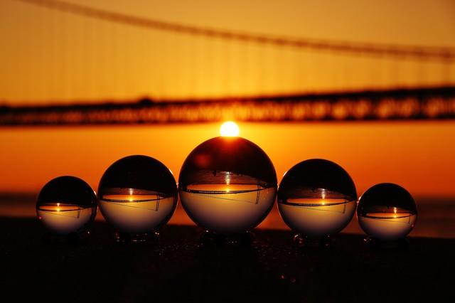 日の出が橋にかかる様子と水晶球の写真