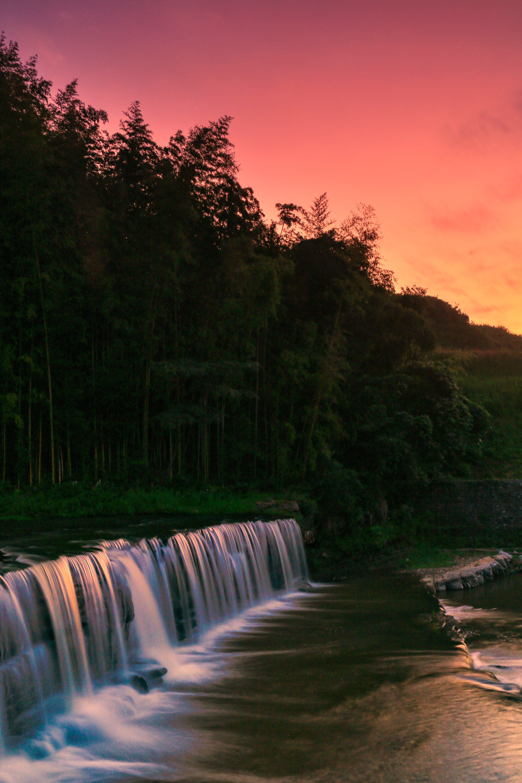 赤く染まる夕刻の空と滝の写真