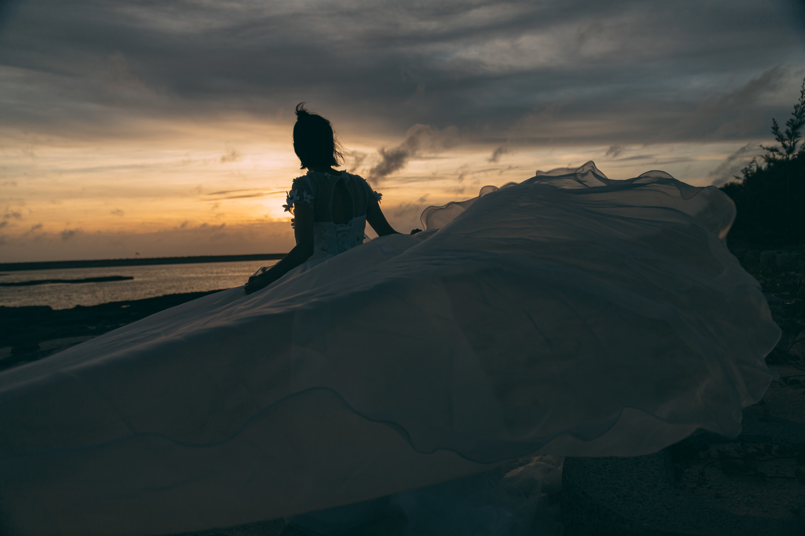 「夕刻の砂浜とウェディングドレスを着た女性」の写真